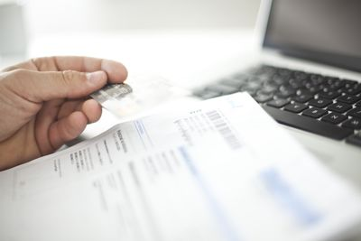 paying bills with debit card and laptop