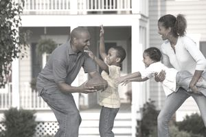 A family of four plays football in front of a home.