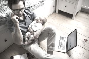 A man sitting on the nursery room floor cradles a baby in one arm while talking on a cellphone. A laptop and a notebook lay open on the floor nearby.