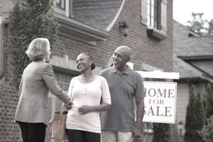 Realtor shaking hands with smiling couple outside house for sale.