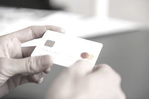 close up of man's hands holding a white credit card
