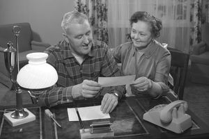 an older couple holding a piece of paper at a desk