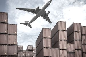A plane flying over a shipping yard with stacks of shipping containers