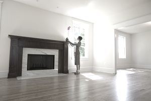 Woman placing a flower in a vase on a mantel in an empty living room