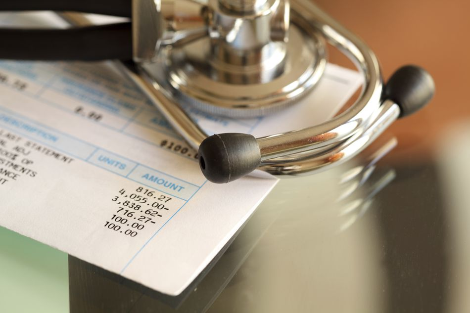 A stethoscope sits atop an outstanding medical bill