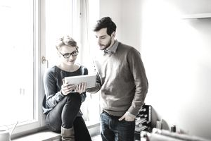 Two business people look at tablet while sitting on windowsill