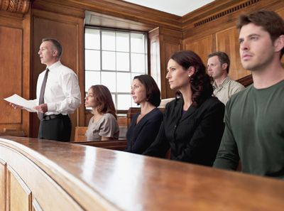 Several people sit along a bench in a courtroom.