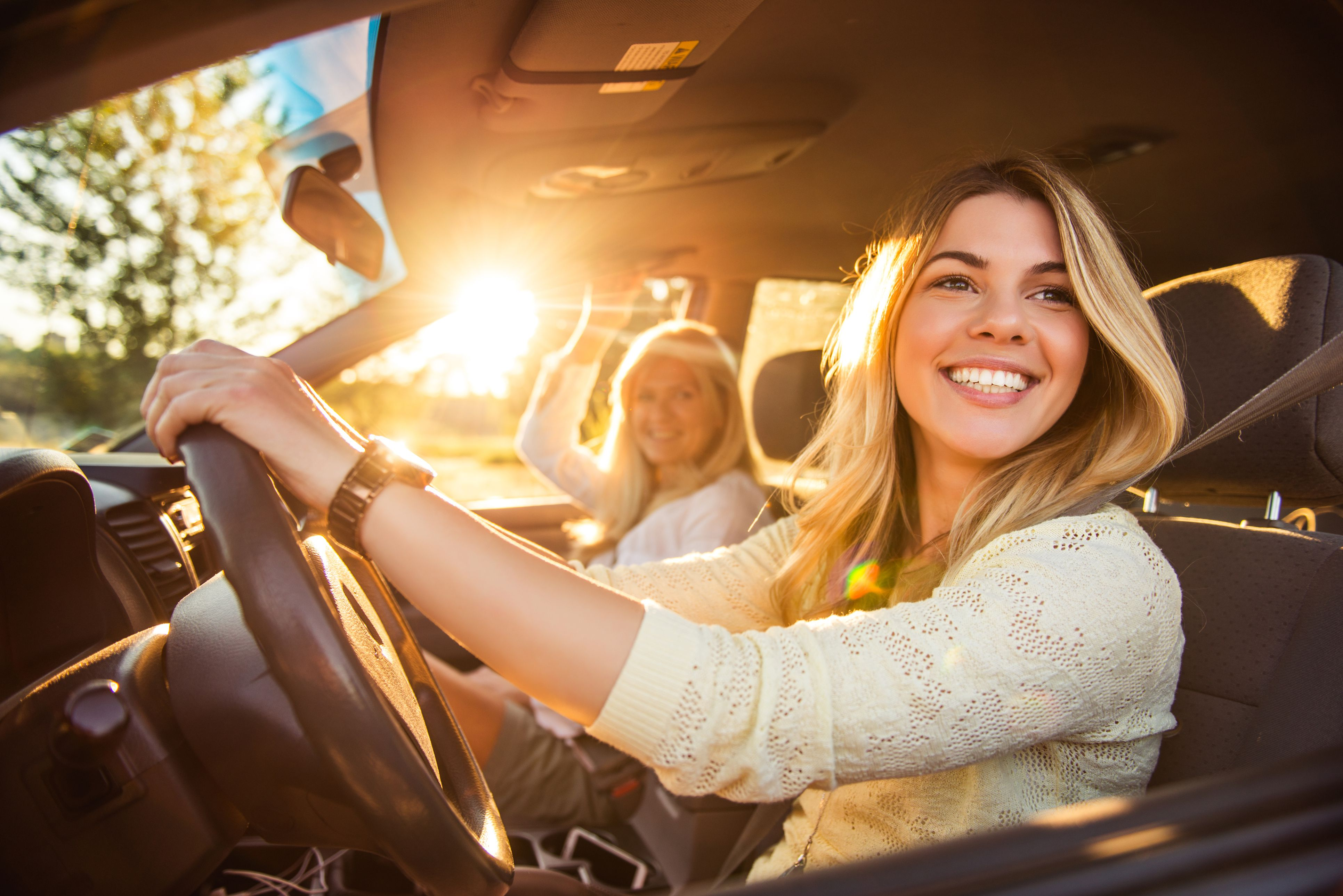 Young woman driving with a friend in the front seat.