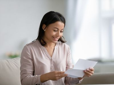Happy young mixed race woman holding and reading paper letter