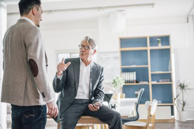 Senior businessman talking to young businessman in office