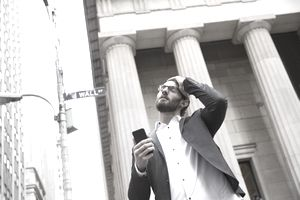 Frustrated businessman standing in front of the stock exchange on Wall Street with his cellphone.