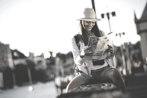 A woman sitting on a park bench near a waterway reviews a map.