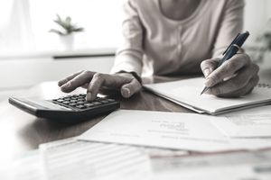 Woman using a calculator to track savings and spending