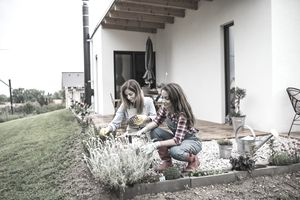 Mother and daughter gardening outside home