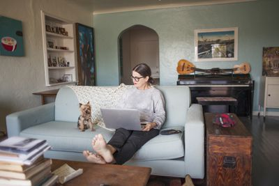 A woman wearing eyeglasses sitting on a blue sofa in her creative home with her laptop computer and small dog