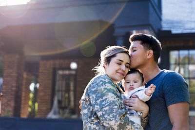 Soldier holding baby is kissed by her husband