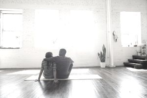 Couple sitting on the floor in an empty, new home