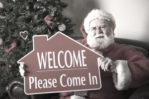 Santa Claus holding an open house sign