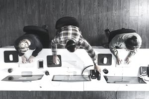 An overhead photograph of a trio of telemarketers seated at a long desk, typing and answering the phone.