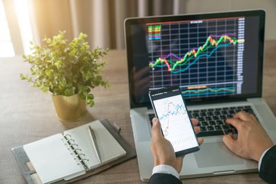 Investor analyzing stock market investments using a laptop and a smartphone