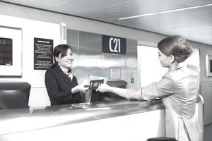 Airline employee with customer at airport counter
