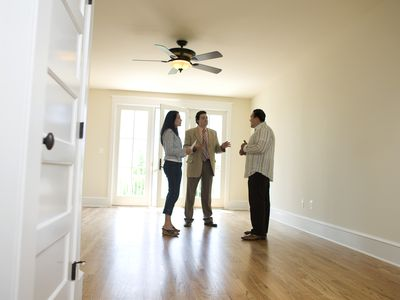 Home buyers with real estate agent in empty home