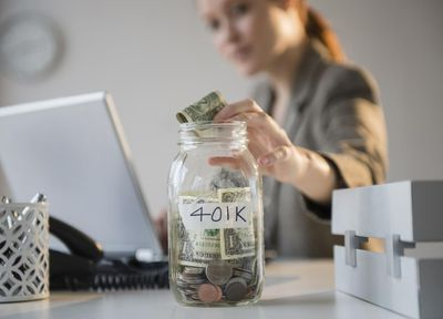 A young woman putting money into jar on her desk labeled 401K.