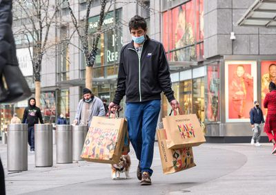 A person wears a face mask while carrying shopping bags.
