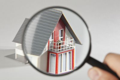 Hand holding a magnifying glass up to a model home representing home inspection