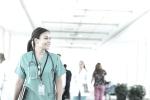 Cheerful Latino Nurse With Stethoscope Walks in Hospital Halls