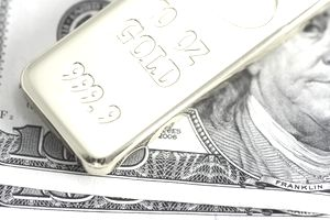 Gold bar laying on top of U.S. Currency