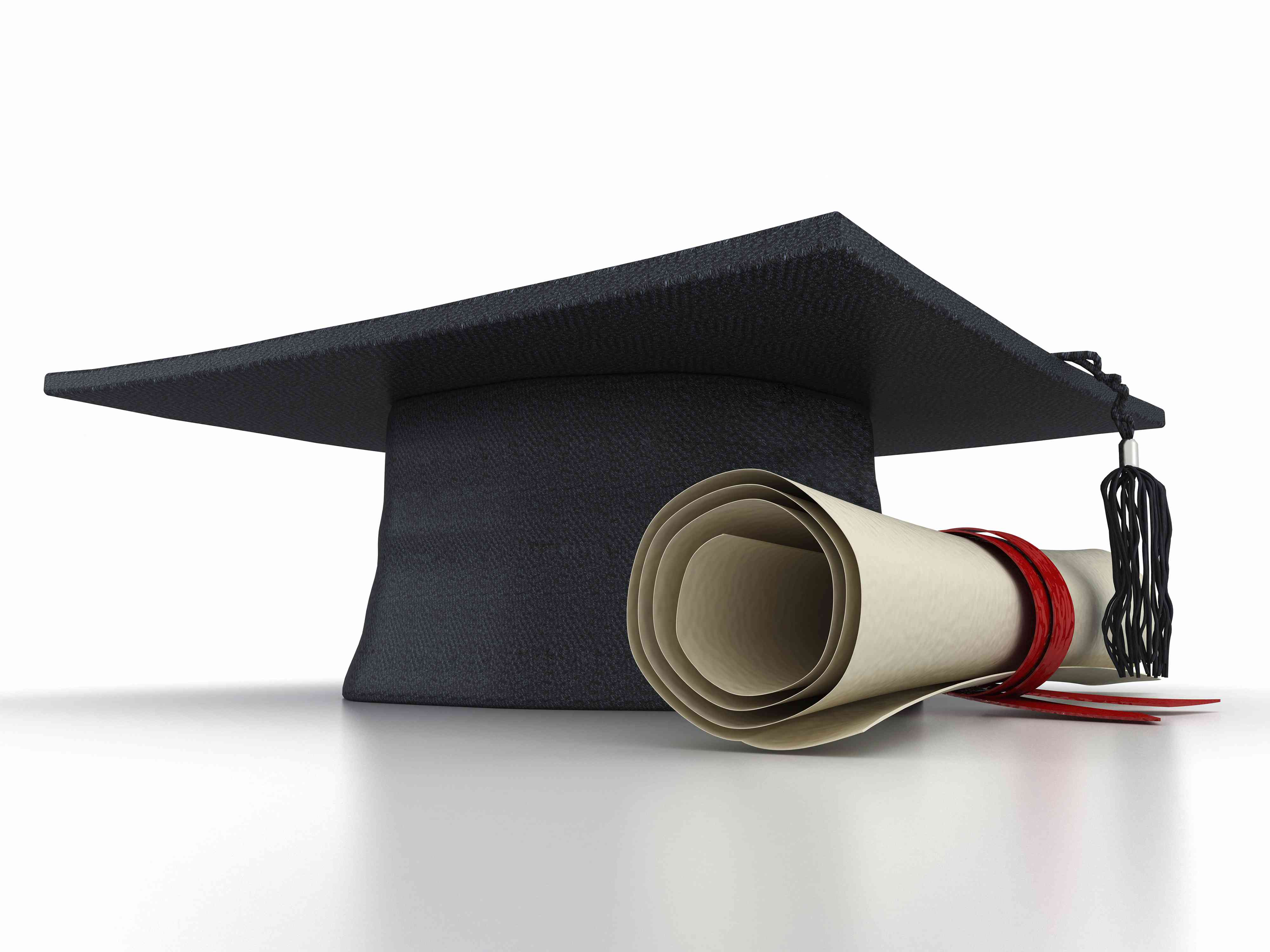 a rolled diploma tied with a ribbon lays next to a mortarboard cap