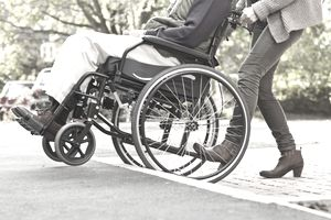 Woman pushing man in wheelchair up step or ramp onto pavement