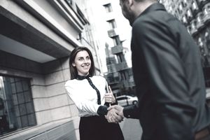 young businesswoman shaking hands with a man in a suit