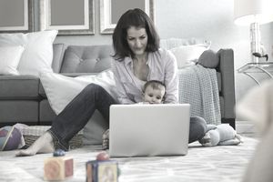 Mother with baby using laptop in living room