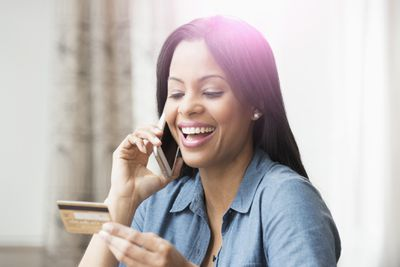 A woman speaking on a smartphone smiles as she changes her name on her credit card.
