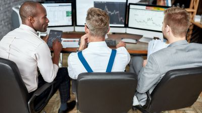Three traders look at computers and compare data analyses