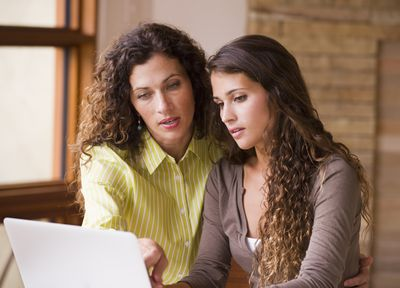 Sisters looking at a computer and discussing family finances