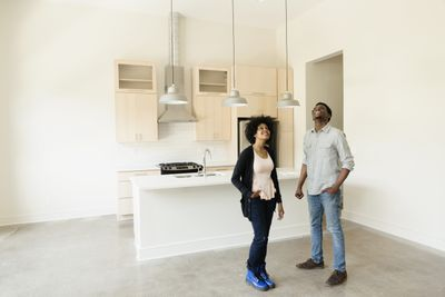 Smiling couple standing in the vacant kitchen of their first home