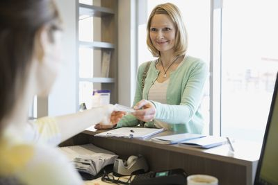 A receptionist taking a patient's insurance card in a dentist's office