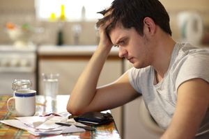 Young man fretting over student loan bills