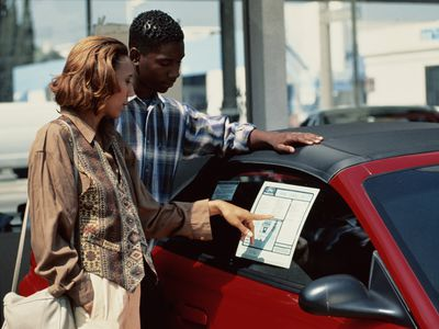 A woman choosing a new car and looking at dealership fees on window sticker