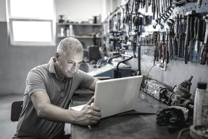 business owner in grey collared shirt working on computer inside his repair shop