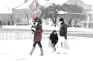 Family walking in the snow carrying bags.