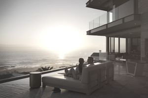 Tranquil sunset ocean view beyond silhouette of couple on luxury home