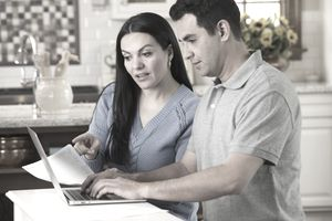 Hispanic couple paying bills on laptop