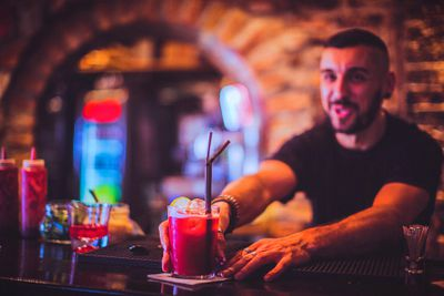 Close-up of young bartender serving cocktail in nightlife bar