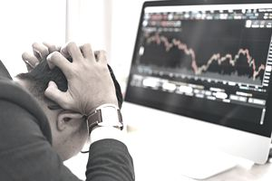 Trader clutching his head as he sits before computer monitor showing market prices