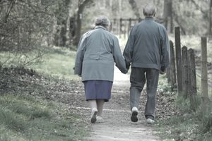Older couple holding hands and walking on a path in the woods