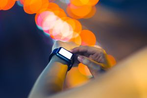 Human hands using smart watch outdoors at night